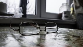 on the kitchen table covered with a tablecloth are metal-framed glasses royalty free stock photo