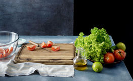 Kitchen table with cutting board, salad bowl and vegetables Royalty Free Stock Photos