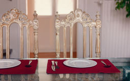 The kitchen  table porcelain plates fork , knife , and two vintage chair against the window Stock Images