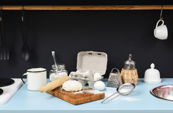 Kitchen table in process of making homemade cookies. Raw dough,. Rolling pin, sieve, eggs, flour and kitchen utencils on black and blue background with stock image