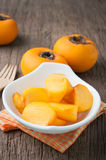 Kitchen table with slice fresh orange persimmon on white plate a Royalty Free Stock Photography
