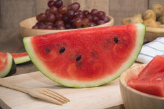 Kitchen table with Sliced of Watermelon on cutting board and grape fruit. Royalty Free Stock Image