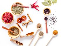 Kitchen table with spices and dry herbs on white kitchen background top view pattern Royalty Free Stock Image
