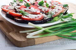 Kitchen table with stewed eggplant and tomato slices Royalty Free Stock Photo