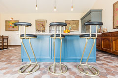 Kitchen with a table top and bar stools Royalty Free Stock Photography