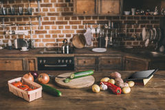 Kitchen table with variety of raw vegetables Stock Photos