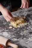 On a kitchen table the women`s hands kneads the dough. Step-by-step preparation of the dough stock photo