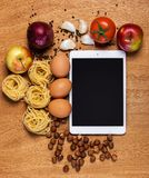 Kitchen. Tablet and food Royalty Free Stock Photos