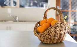 Kitchen tabletop and basket of oranges Stock Image