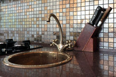 Kitchen tap in retro style. Kitchen tap in retro style with knives in background stock photography
