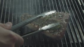 Kitchen tongs shift the frying steak stock video footage
