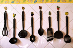 Kitchen Tools. Collection of used kitchen tools hanged on a tile wall with vegetable shaped holders stock photography