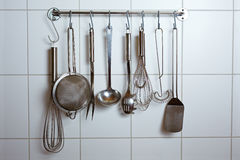 Kitchen tools. Many different kitchen tools on hooks in a kitchen Royalty Free Stock Photography