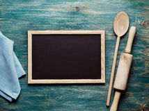 Kitchen tools. Blank black board on wooden table and kitchen tools Royalty Free Stock Photography