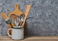 Free Kitchen Tools For Cooking On A Wooden Table On The Background Of A Concrete Wall.Copy Space. Spoons, Forks, Wooden Spatula Stock Photos - 112797193