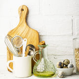 Kitchen tools, olive cutting board on a kitchen shelf against a white brick wall. selective focus Stock Images