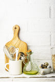 Kitchen tools, olive cutting board on a kitchen shelf against a white brick wall. selective focus. Kitchen tools, olive cutting board on a kitchen shelf against Stock Photography