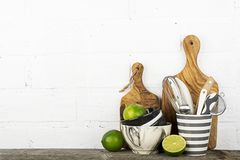 Kitchen tools, olive cutting board on a kitchen shelf against a white brick wall. selective focus.  Royalty Free Stock Images