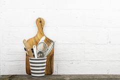 Kitchen tools, olive cutting board on a kitchen shelf against a white brick wall. selective focus.  Royalty Free Stock Photos