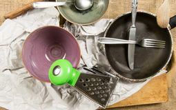 Kitchen tools - two bowls, fork, knife, wooden spoon, pan, grater and paper Royalty Free Stock Photos