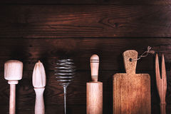 Kitchen tools on a wooden background. Applied toning. Top view. Royalty Free Stock Images