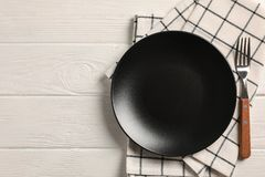 Kitchen towel with cutlery on wooden background. Top view royalty free stock photos