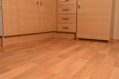Kitchen units and wooden floor. Closeup of wooden kitchen units with laminate floor stock photo