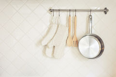 Kitchen utensil Glove and Pan Wooden Spoon on Tiles wall. Kitchen utensil Glove and Pan with Wooden spoon Fork on white Tile wall Royalty Free Stock Photos