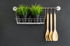 Kitchen utensil hang on black wall Royalty Free Stock Images