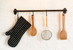 Kitchen utensil hang. On white stone wall Royalty Free Stock Images