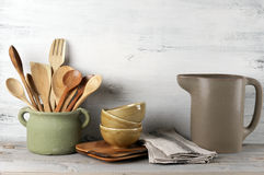 Kitchen utensil set. Simple rustic kitchenware against white wooden wall: rough ceramic pot with wooden cooking utensil set, stacks of ceramic bowls, jug and Stock Images