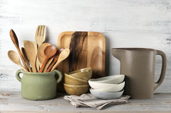 Kitchen utensil set. Simple rustic kitchenware against white wooden wall: rough ceramic pot with wooden cooking utensil set, stacks of ceramic bowls, jug and Royalty Free Stock Photo