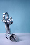Kitchen utensil, steel meat grinder components, blue background. Free copy space. Stock Images