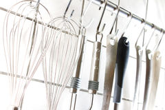 Kitchen utensils. Lots of kitchen utensils on a rod Stock Images