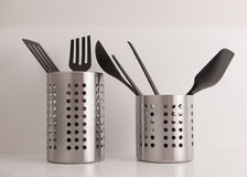 Utensils in stainless steel container. Black plastic kitchen utensils in stainless steel containers on white shelf Stock Photography