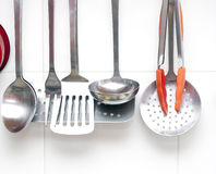 Kitchen utensils. Hanging against a white tiled wall royalty free stock image
