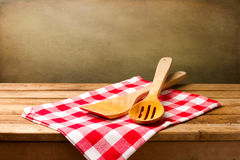 Kitchen utensils. On tablecloth on wooden table over grunge background Royalty Free Stock Photography