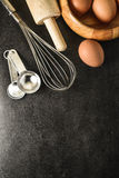Kitchen utensils and baking ingredients: egg and flour on black background. Royalty Free Stock Images