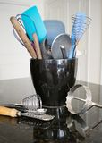 Kitchen utensils in black container on counter. Several kitchen utensils stuffed in a black ceramic container on a black granite counter with some utensils on royalty free stock images