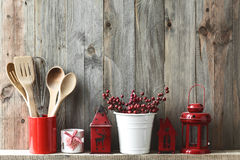 Kitchen utensils. Kitchen cooking utensils in ceramic storage pot and Christmas decor on a shelf on a rustic wooden wall stock image