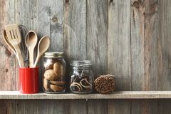 Kitchen utensils. Kitchen cooking utensils in ceramic storage pot and cookies on a shelf on a rustic wooden wall royalty free stock photos