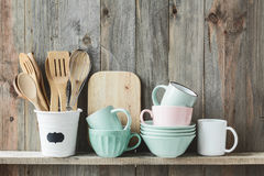Kitchen utensils. Kitchen cooking utensils in ceramic storage pot on a shelf on a rustic wooden wall royalty free stock image