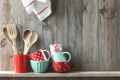 Kitchen utensils. Kitchen cooking utensils in ceramic storage pot on a shelf on a rustic wooden wall, space for text royalty free stock photo
