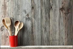 Kitchen utensils. Kitchen cooking utensils in ceramic storage pot on a shelf on a rustic wooden wall, space for text stock image