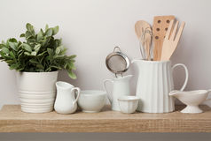 Kitchen utensils and dishware on wooden shelf. Kitchen interior background royalty free stock images