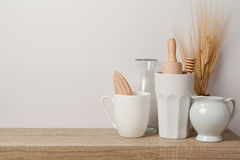 Kitchen utensils and dishware. On wooden shelf. Kitchen interior background stock photography