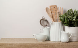 Kitchen utensils and dishware. On wooden shelf. Kitchen interior background royalty free stock photography
