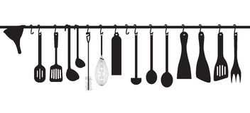 Kitchen utensils hanging on the chromed bar Royalty Free Stock Photos