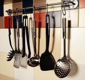 Kitchen utensils hanging on a colored  tile wall. Background Royalty Free Stock Photography