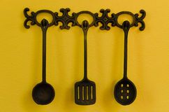 Kitchen utensils hanging on yellow background Stock Photography